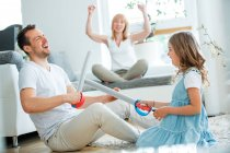 Father and daughter fighting with toy swords, mother cheering in background — Stock Photo