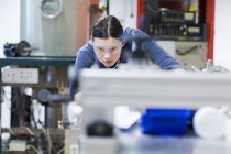 Young woman with safety goggles working at machine — Stock Photo