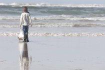 Ragazzo che gioca con barca a vela giocattolo sulla spiaggia — Foto stock