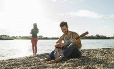 Young man playing guitar with woman by the riverside — Stock Photo