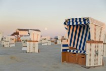 Germany, North Sea, wicker chairs on the beachfront in the evening — Stock Photo