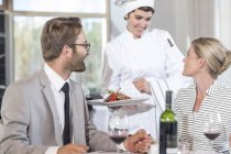 Chef serving food for mid adult couple — Stock Photo