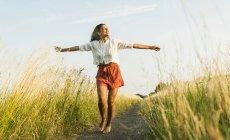 Молодая женщина, стоя с вытянутыми руками на пути в поле — стоковое фото