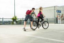 Happy young couple with bicycle and skateboard — Stock Photo