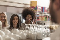 Young women ordering at the coffee bar, smiling — Stock Photo