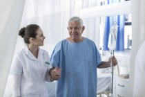 Nurse supporting senior patient in hospital — Stock Photo