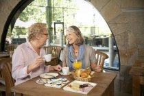 Avendo la colazione in un caffè di coppie maggiori sorridenti — Foto stock