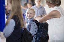 Teacher helping schoolgirl with backpack on hallway — Stock Photo