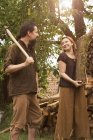 Smiling couple with axe and firewood — Stock Photo