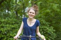 Ritratto di giovane donna sorridente in bicicletta — Foto stock