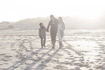 Young couple and son walking on the beach — Stock Photo
