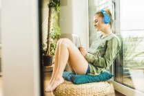 Teenage girl lying at home listening to music from digital tablet — Stock Photo