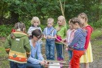 Діти, як побудувати дерев'яний пліт в природі — стокове фото