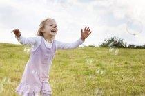 Chica rubia captura de burbujas de jabón en el prado - foto de stock