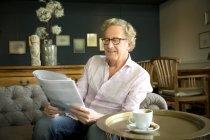 Smiling senior man in lounge room reading magazine — Stock Photo