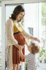Маленький мальчик указывает на живот своей беременной матери дома — стоковое фото