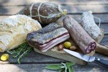 Cerca de diferentes embutidos, pan y aceitunas en la tajadera - foto de stock