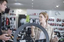 Young salesman and client looking at bicycles — Stock Photo