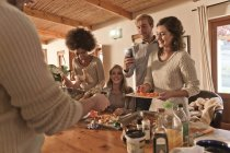 Friends preparing meal together at modern kitchen — Stock Photo