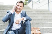 Бизнесмен сидит на лестнице с помощью смартфона — стоковое фото