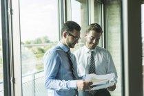 Dois jovens empresários olhando para documentos na janela — Fotografia de Stock