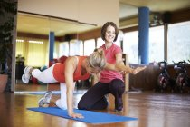 Woman exercising with coach in fitness studio — Stock Photo