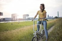 Woman with bicycle on meadow — Stock Photo