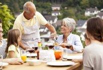 Großvater mit Speisen aus Barbecue-Grill für Familie am Gartentisch — Stockfoto