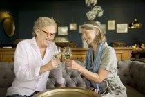 Улыбаясь Пожилые супружеские пары, сидя на диване в гостиной звон бокалов — стоковое фото