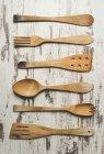 Fila de seis utensilios de cocina de madera diversos en fondo madera - foto de stock