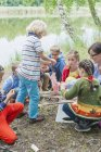 Children learning how to build wooden raft in nature — Stock Photo