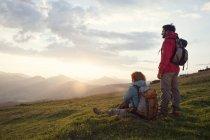 Австрия, Тироль, Unterberghorn, двух туристов, отдыхая в альпийских пейзажей на рассвете — стоковое фото
