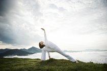 Austria.Kranzhorn, Mujer adulta que practica yoga en la cima de la montaña - foto de stock