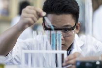Student in chemistry class pipetting liquid into test tube — Stock Photo