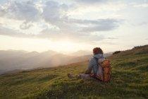 Австрия, Тироль, Unterberghorn, турист отдыхает в альпийских пейзажей на рассвете — стоковое фото