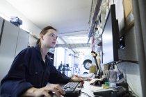 Jeune femme travaillant dans un garage de réparation, rédaction du rapport de contrôle — Photo de stock