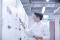Homme technicien en peignoir blanc machine d'examen — Photo de stock