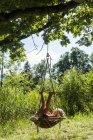 Girl relaxing in nest swing — Stock Photo