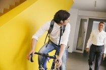 Mann mit dem Fahrrad in einem Büro racing — Stockfoto
