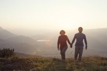Austria, Tyrol, couple walking hand in hand at Unterberghorn at sunset — Stock Photo
