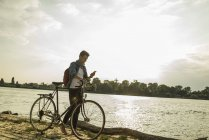 Young man with bicycle and cell phone by the riverside — Stock Photo