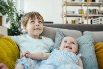Baby Girl und Bruder auf Couch nachschlagen — Stockfoto