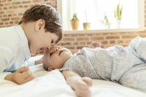 Малышка и брат обнимаются дома — стоковое фото