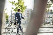 Молодой бизнесмен толкает велосипеды, держит смартфон — стоковое фото