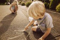 Дети, использующие мел на тротуаре в своем районе — стоковое фото