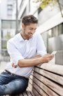 Portrait of smiling man sitting on wooden bench while looking at his smartphone — Stock Photo