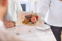 Chef serving main dishto couple in restaurant — Stock Photo