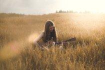 Женщина играет на гитаре в поле — стоковое фото