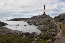 Lighthouse by the rocky coast view — Stock Photo