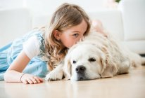Маленькая девочка обнимается со своей собакой, лежит на полу — стоковое фото